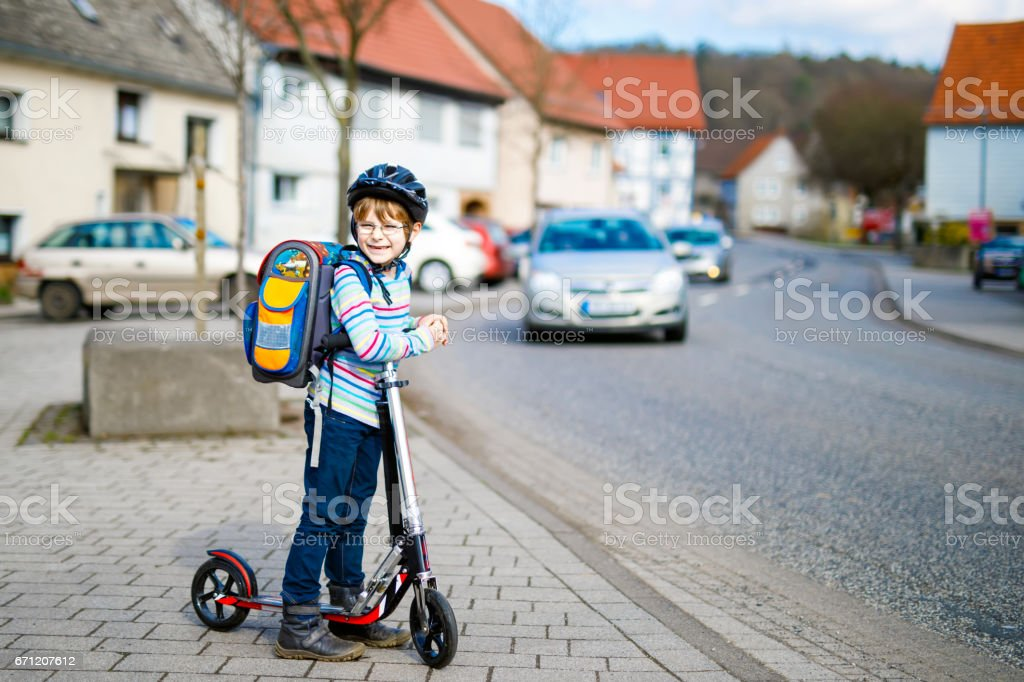Little kid boy in helmet riding with his scooter in the city stock photo
