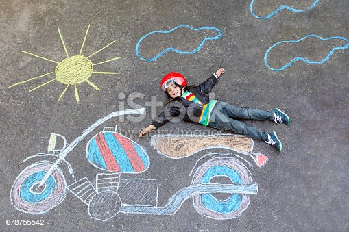 istock Little kid boy in helmet with motorcycle chalk picture 678755542