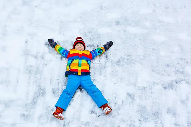 kleines kind junge machen schnee-engel im winter im freien - schneespiele stock-fotos und bilder