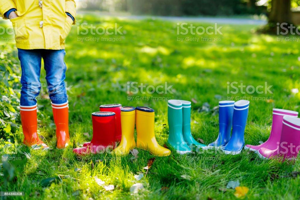 Kleines Kind, junge oder Mädchen in Jeans und gelbe Jacke in bunten Regen Stiefel. – Foto