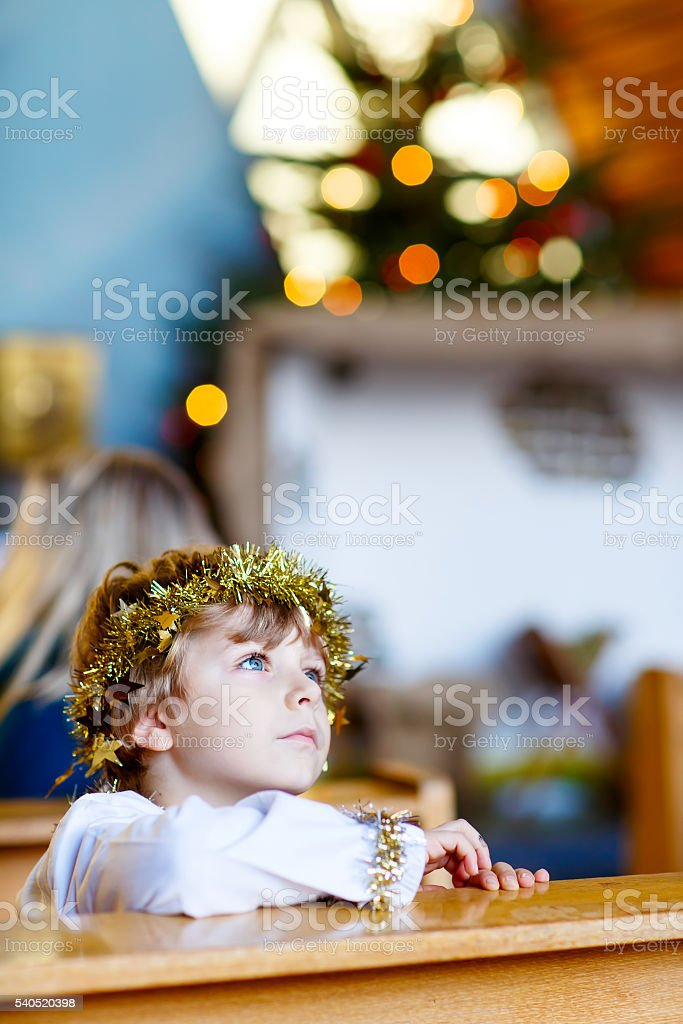 little kid boy playing angel of Christmas story in church stock photo