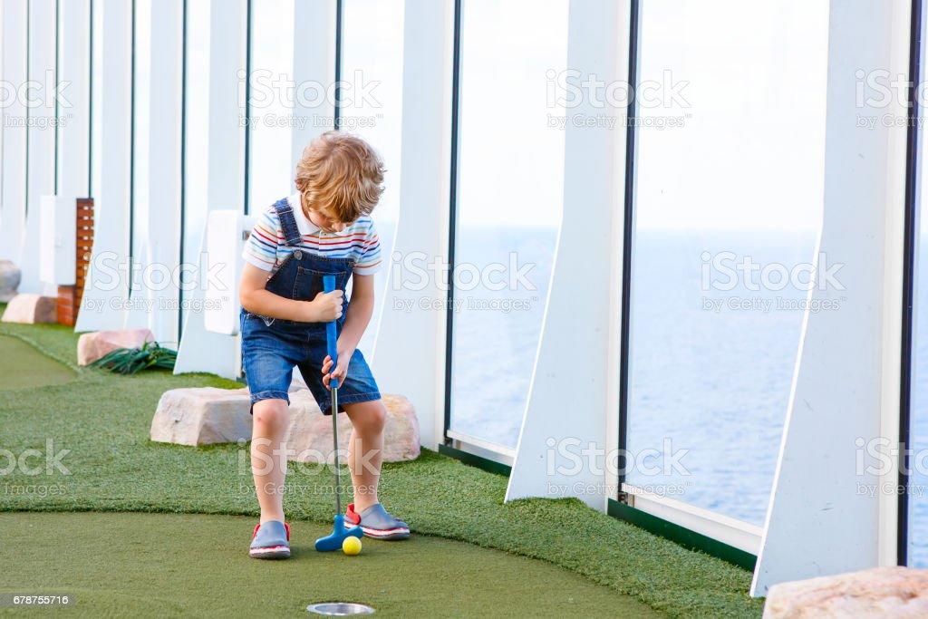 Petit garçon enfant jouer au mini golf sur un paquebot de croisière. photo libre de droits