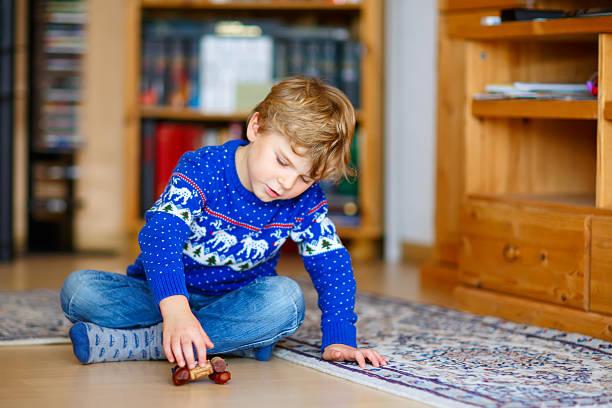 little kid boy playing with handmade chestnut toy indoors - kastanientiere stock-fotos und bilder