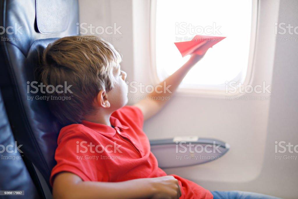 Kleine Kind Junge spielt mit rotem Papierflugzeug während des Fluges im Flugzeug – Foto