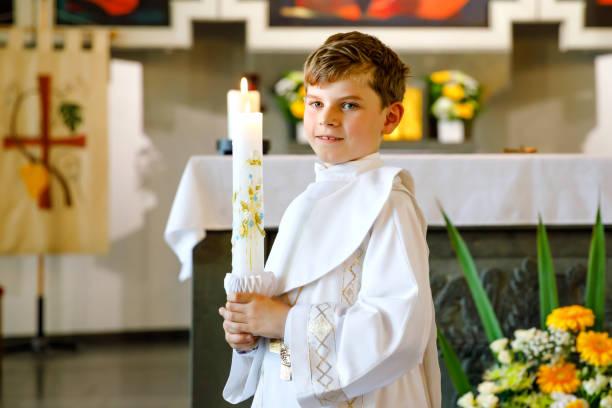 Kleiner Junge, der seine erste heilige Kommunion empfängt. Glückliches Kind hält Taufkerze. Tradition in katholischer Kurve. Kind in einem weißen Trachtenkleid in einer Kirche in der Nähe des Altars. – Foto