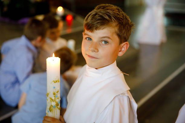 Little kid boy receiving his first holy communion. Happy child holding Christening candle. Tradition in catholic curch. Kid in a white traditional gown in a church near altar. Little kid boy receiving his first holy communion. Happy child holding Christening candle. Tradition in catholic curch. Kid in a white traditional gown in a church near altar clergy stock pictures, royalty-free photos & images
