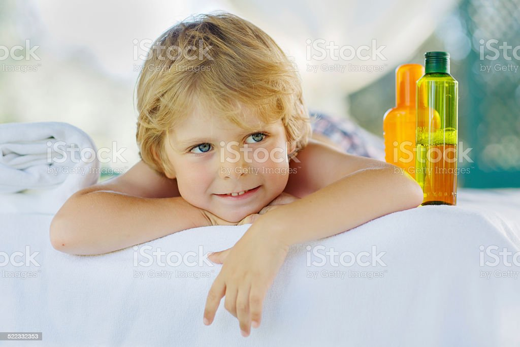 Little kid boy relaxing in spa with enjoying massage Little kid boy relaxing in spa and enjoying massage. Affectionate Stock Photo