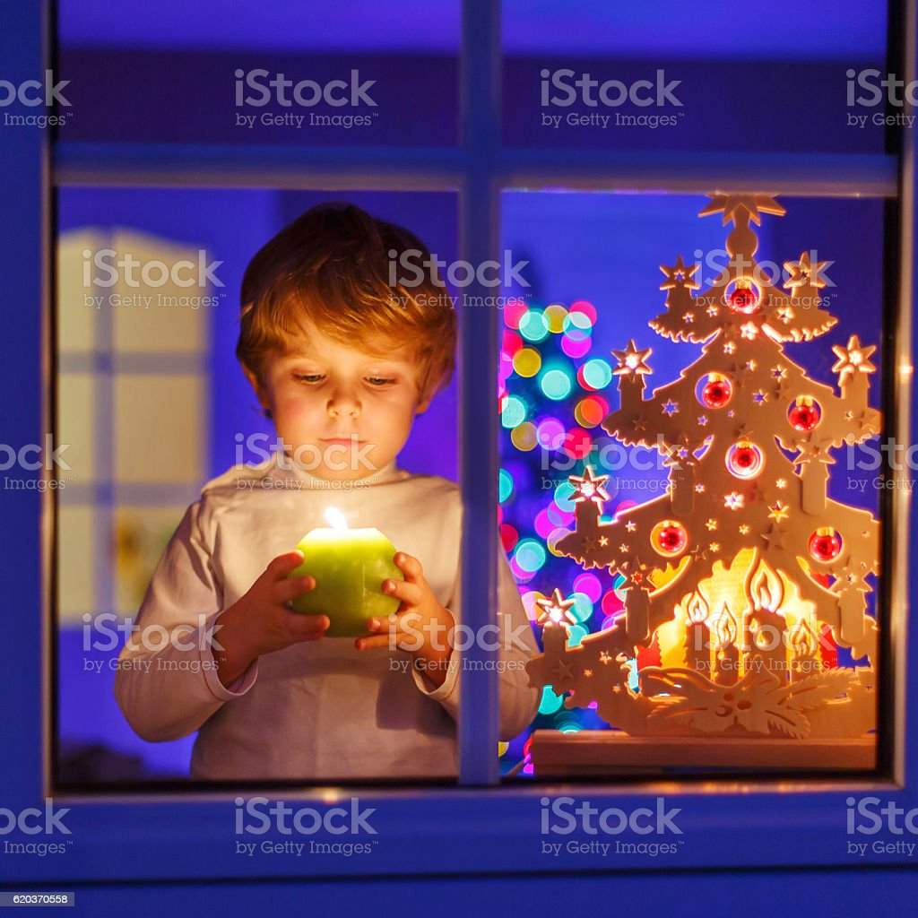 Little kid boy standing by window at Christmas eve foto de stock royalty-free