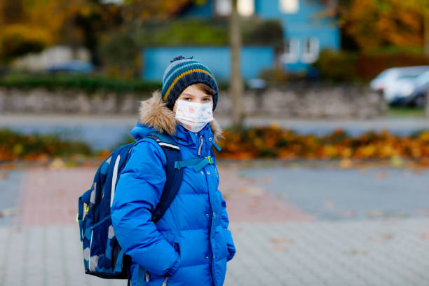 Little kid boy wearing medical mask on the way to school. Child backpack satchel. Schoolkid on cold autumn or winter day with warm clothes. Lockdown and quarantine time during corona pandemic disease stock photo