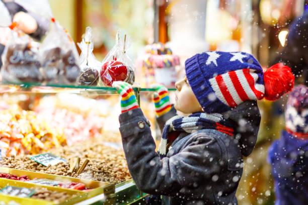 kleine kind junge mit lebkuchen und süßigkeiten stehen auf weihnachtsmarkt - weihnachtsfeier münchen stock-fotos und bilder