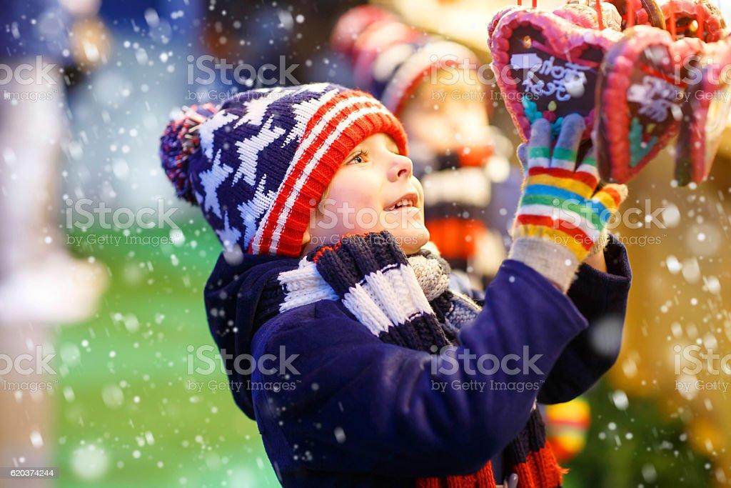 Małe dziecko chłopiec z serca świąteczne z piernika na rynku zbiór zdjęć royalty-free