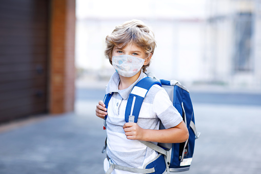 Little kid boy with glasses wearing medical mask on the way to school after lockdown. Child backpack satchel. Schoolkid on warm day with school uniform. Quarantine time during corona pandemic disease