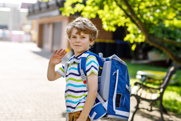 little kid boy with school satchel on first day to school Happy little kid boy with glasses and backpack or satchel on his first day to school or nursery. Child outdoors on warm sunny day, Back to school concept schoolboy stock pictures, royalty-free photos & images