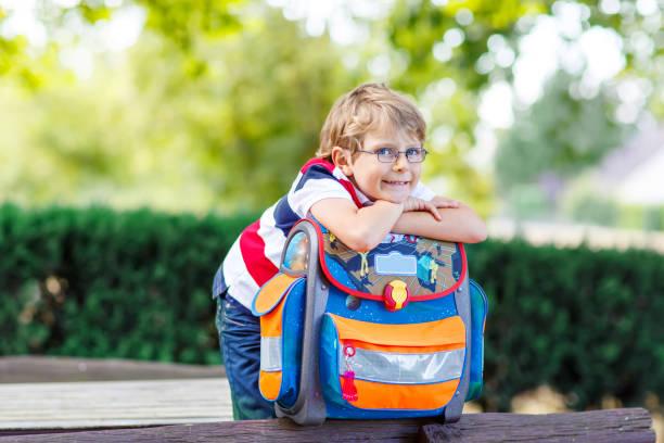 little kid boy with school satchel on first day to school - cartella scolastica foto e immagini stock