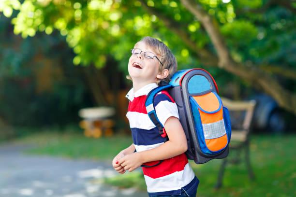 kleine kind junge mit schulranzen schule am ersten tag zur schule - liebeskind umhängetasche stock-fotos und bilder