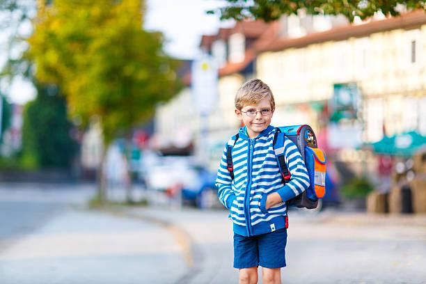 little kid boy with school satchel on way to school - liebeskind umhängetasche stock-fotos und bilder