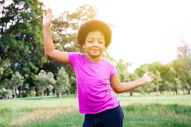 little kid dancing and listening to music in green park - mini amusementpark stockfoto's en -beelden