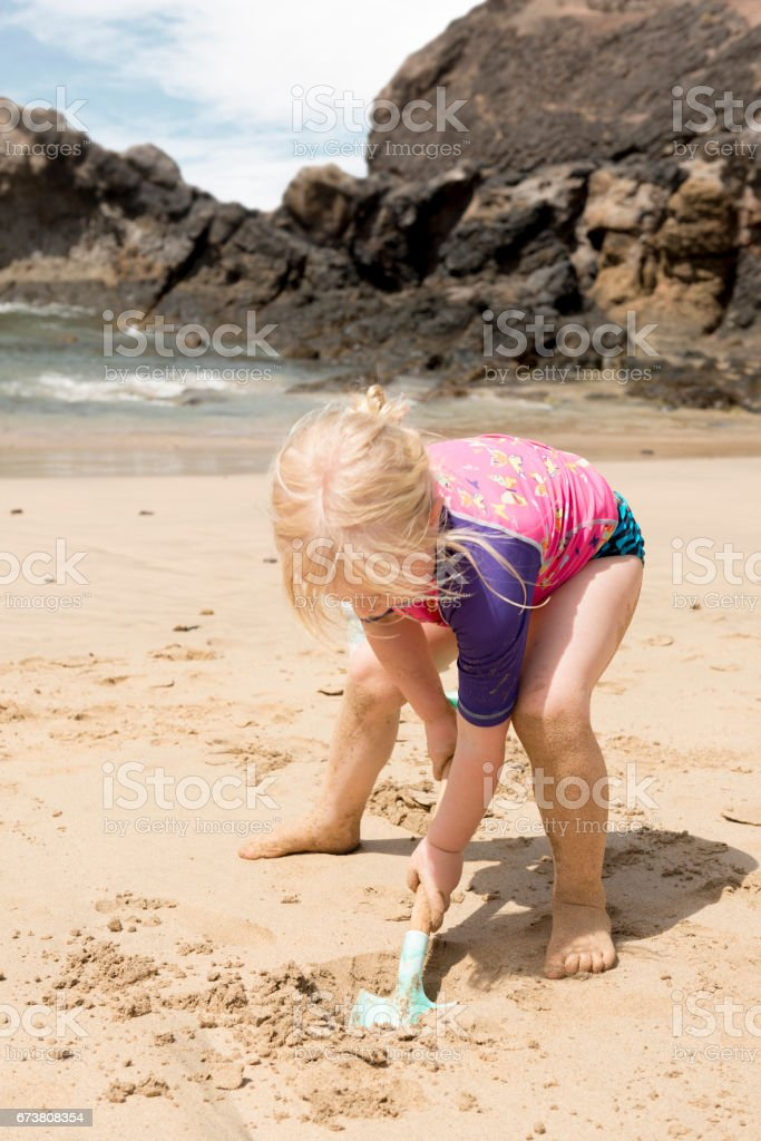 Little Kid Digging Up Sand with Shovel in the Beach photo libre de droits