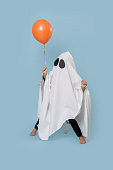 istock Little kid dressed as white ghost on halloween making funny stance 1182419657