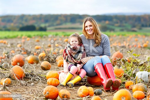 istock Little kid girl and beautiful mother having fun with farming on a pumpkin patch. Traditional family festival with children, thanksgiving and halloween concept. Cute farmers, woman with daughter. 1034956042