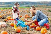 Little kid girl and beautiful mother having fun with farming on a pumpkin patch. Traditional family festival with children, thanksgiving and halloween concept. Cute farmers, woman with daughter