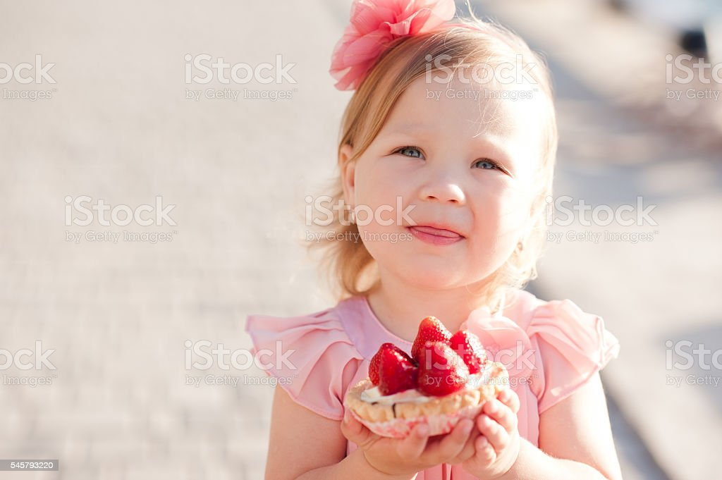 Little kid girl eating cake stock photo