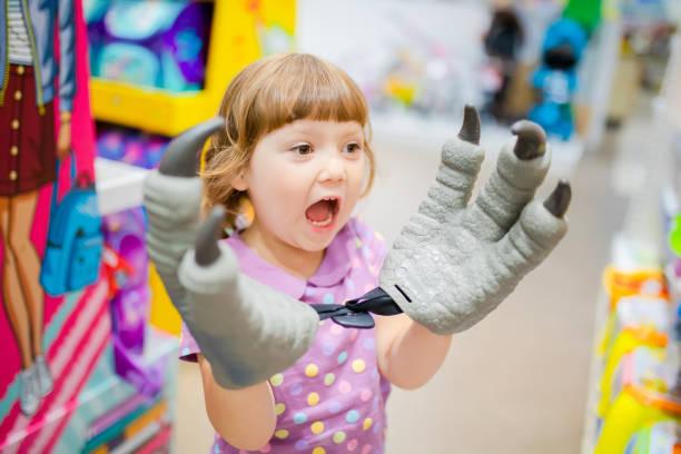 Little kid girl shopper having fun at the toy shop stock photo