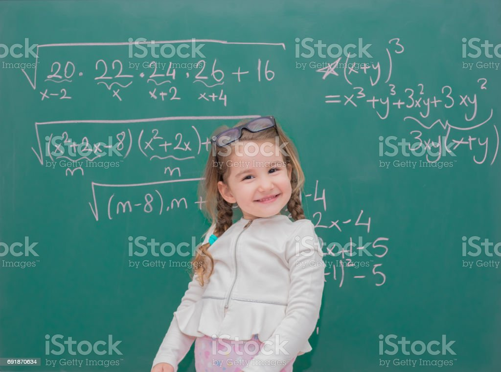 little kid girl teaching in front of the green board stock photo