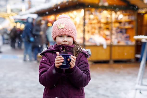 kleines kind mädchen mit heißer schokolade auf weihnachtsmarkt - stoffe berlin stock-fotos und bilder