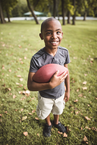 istock little kid happiness with football ball 866052418