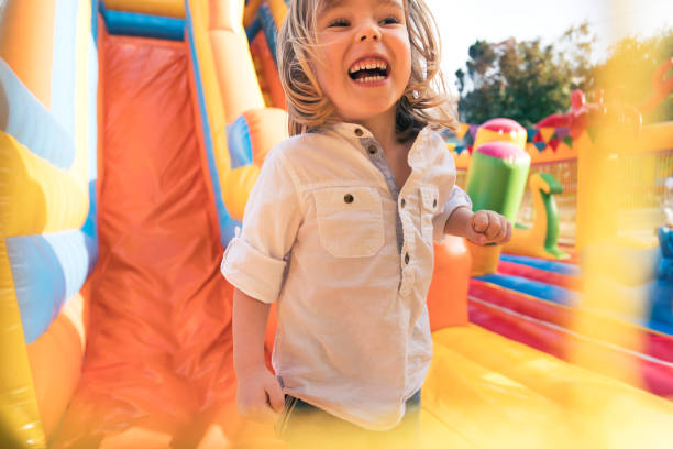 Little kid having fun in inflatable castle playground stock photo