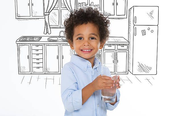 little kid holding a glass of water stock photo