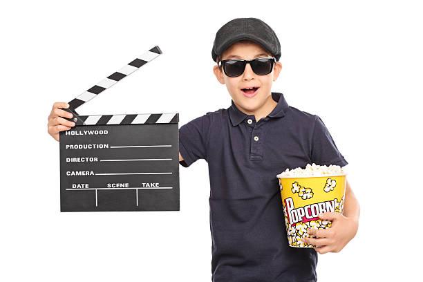 kleines kind holding popcorn und clapperboard - klappe hut stock-fotos und bilder