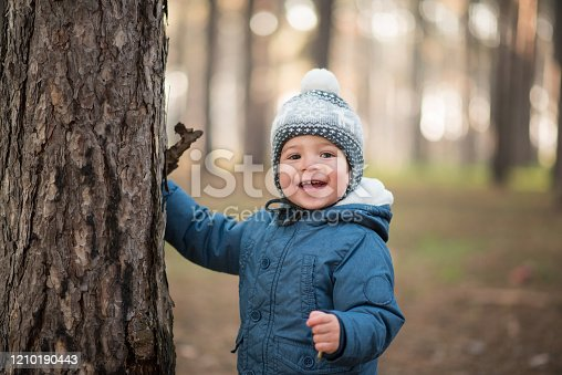Toddler first time outside in the forest, searching and learning about nature, laughing with joy and excitement.