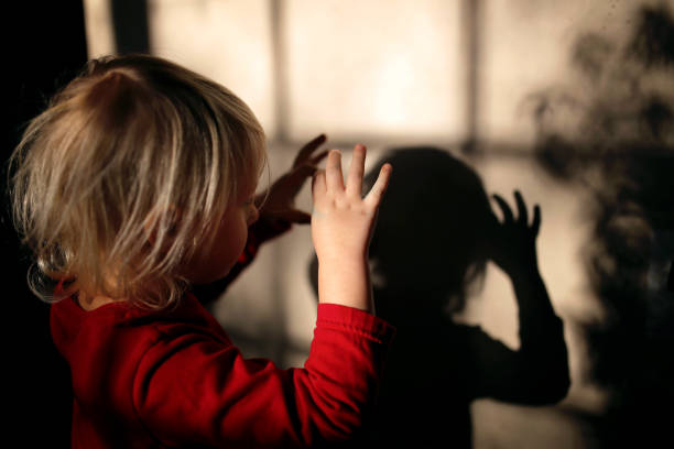 Little Kid Making Shadow Puppets with Fingers on the Wall of her Home stock photo