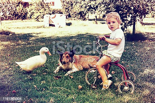 Vintage photo of a blonde kid biking on a tricycle outdoors with a dock and a collie dog by her side.