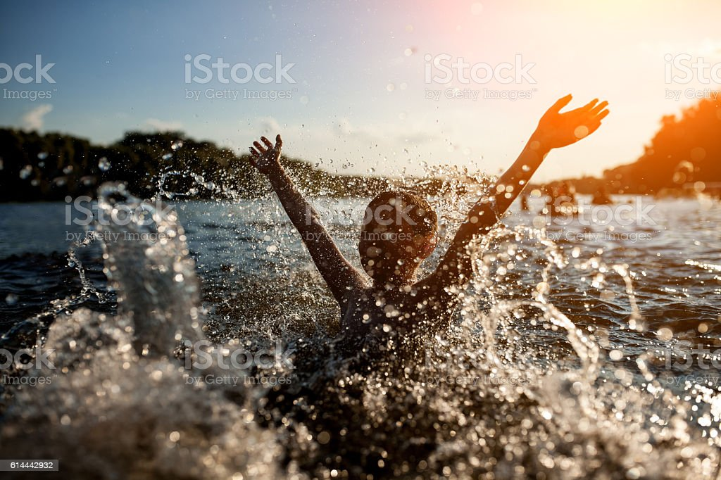 little kid play in water and making splash; – Foto