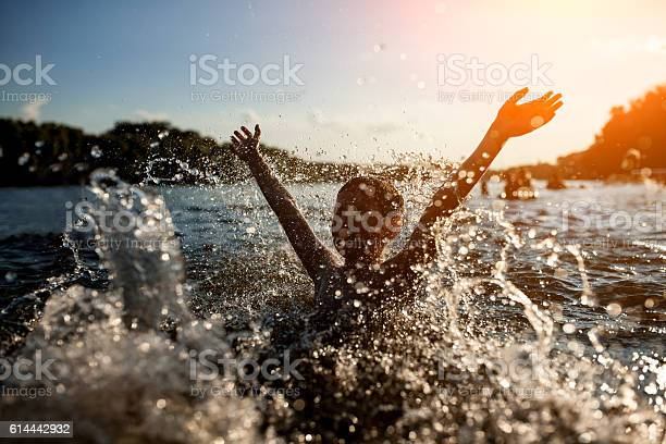 Photo of little kid play in water and making splash;