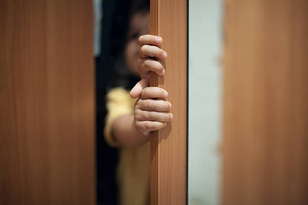 little kid playing hide and seek game; boys hand sticking out of closed door; hide and seek stock pictures, royalty-free photos & images
