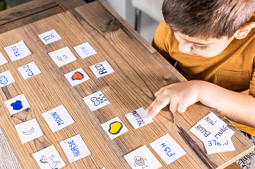Little kid playing with cards of words and pictures.