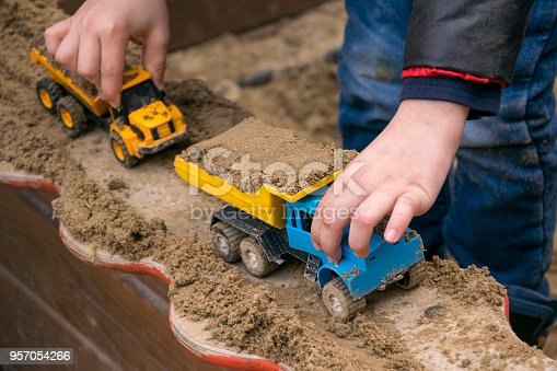 Close up of child hands holding miniature cars. Boy in casual clothes gaming in sandbox with scale models of trucks with grit. Concept of childhood