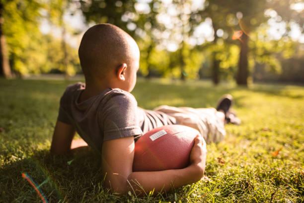 kleines kind mit fußball-ball ruhen - traum team stock-fotos und bilder