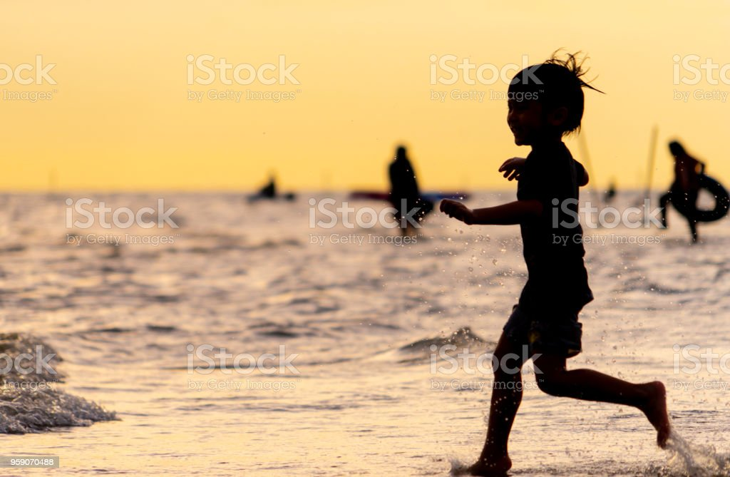 Little kid running on a sand beach silhouette stock photo