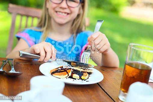 Little happy kid sitting at table and eating pancakes in the morning