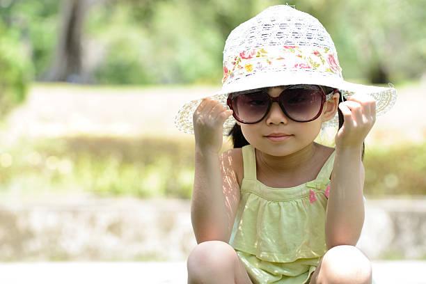 kleines kind sitzt im park - sonnenbrille kleinkind stock-fotos und bilder