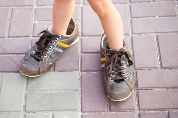 Little kid wearing adults sneakers picture id828213484?b=1&k=6&m=828213484&s=612x612&w=0&h=0z uc502pr3qmii3nxguzrxhofzojhpc ngkkv bt g=