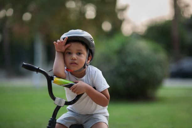 A little kid who looks exhausted or shows the difficulty in riding a bike for the first time by holding his hand to his forehead and looking unhappy. stock photo