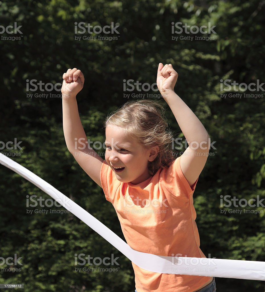A little kid winning a race and tearing a white ribbon stock photo