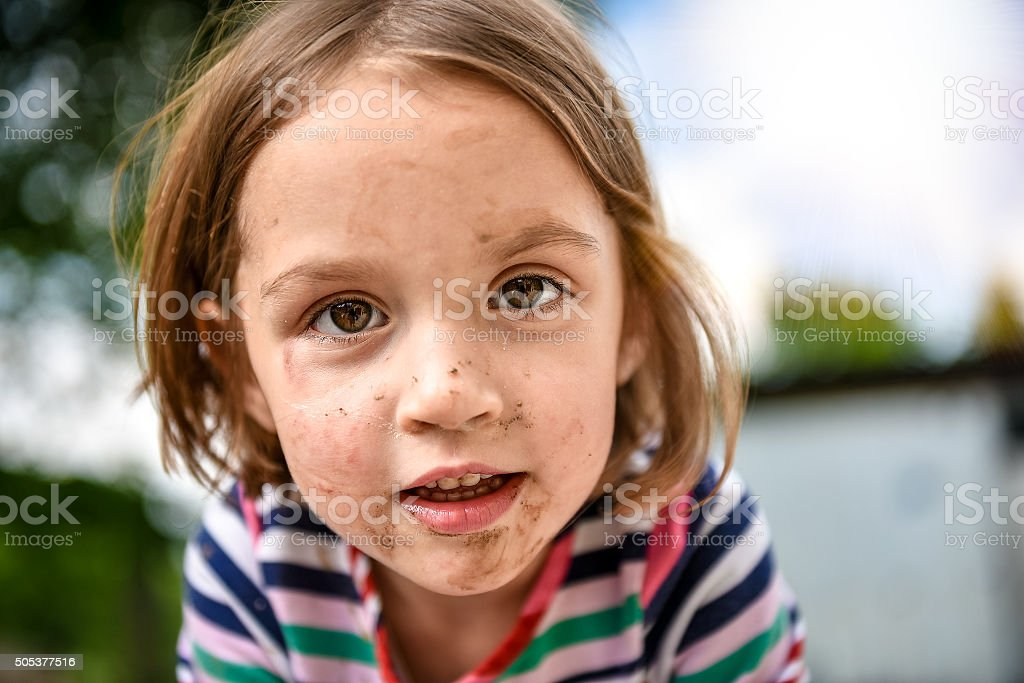 Little kid with dirty face from playing outside in dirt stock photo