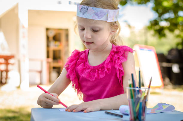 little kid with indian headband drawing with colorful pencils